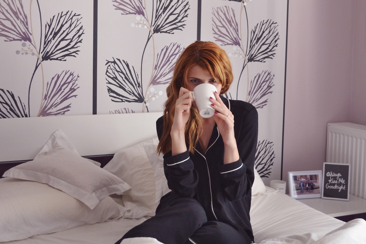 red haired woman drinking tea in bed