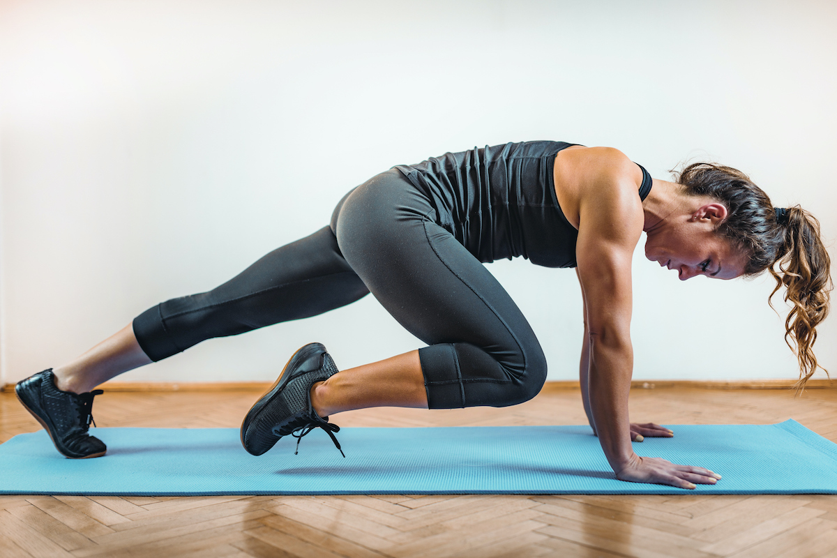 woman on yoga mat doing HIIT workout at home