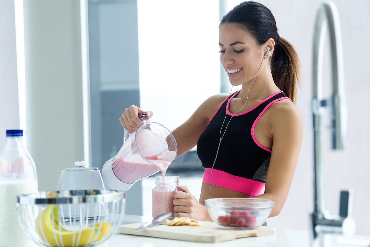 woman smiling making smoothie before workout
