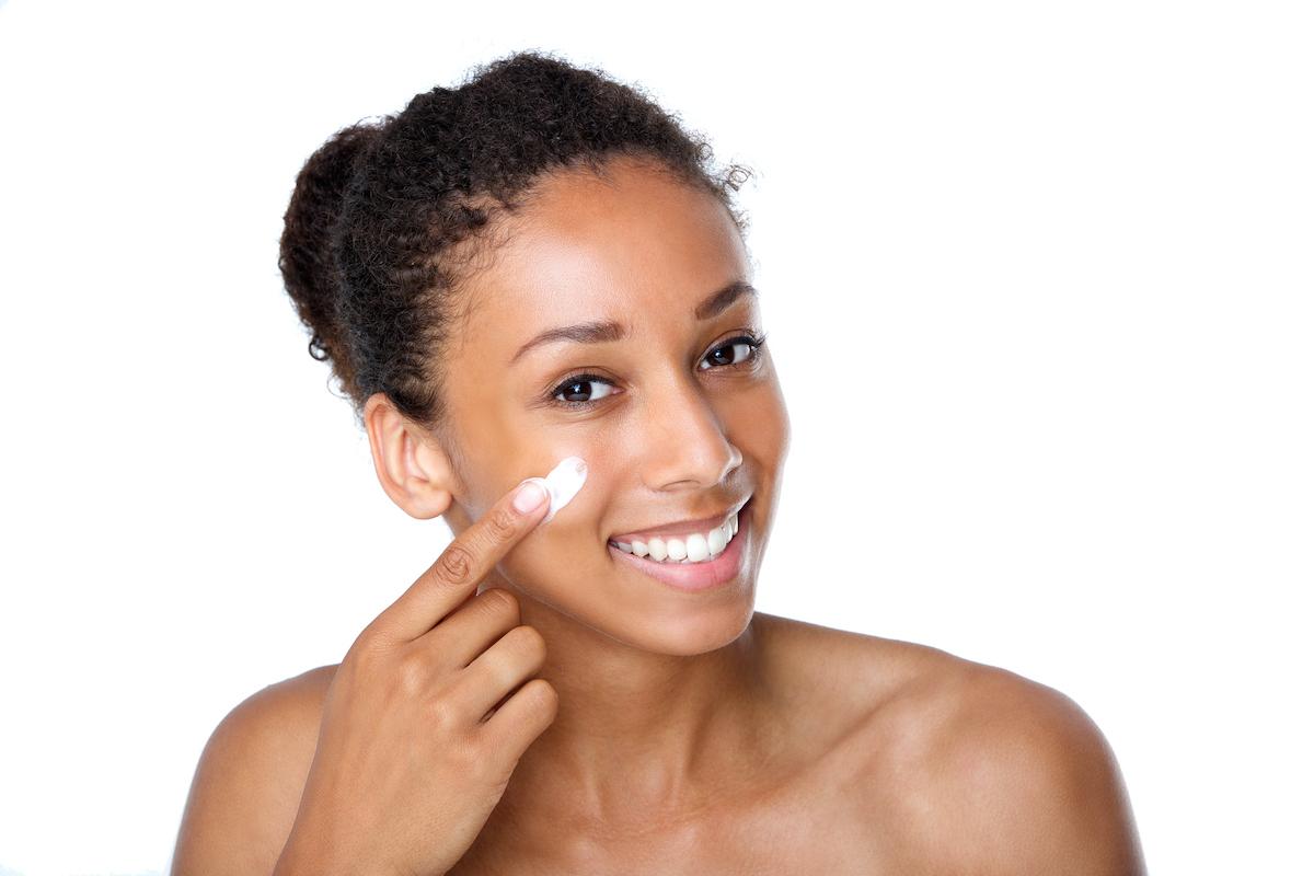BIPOC woman applying skincare