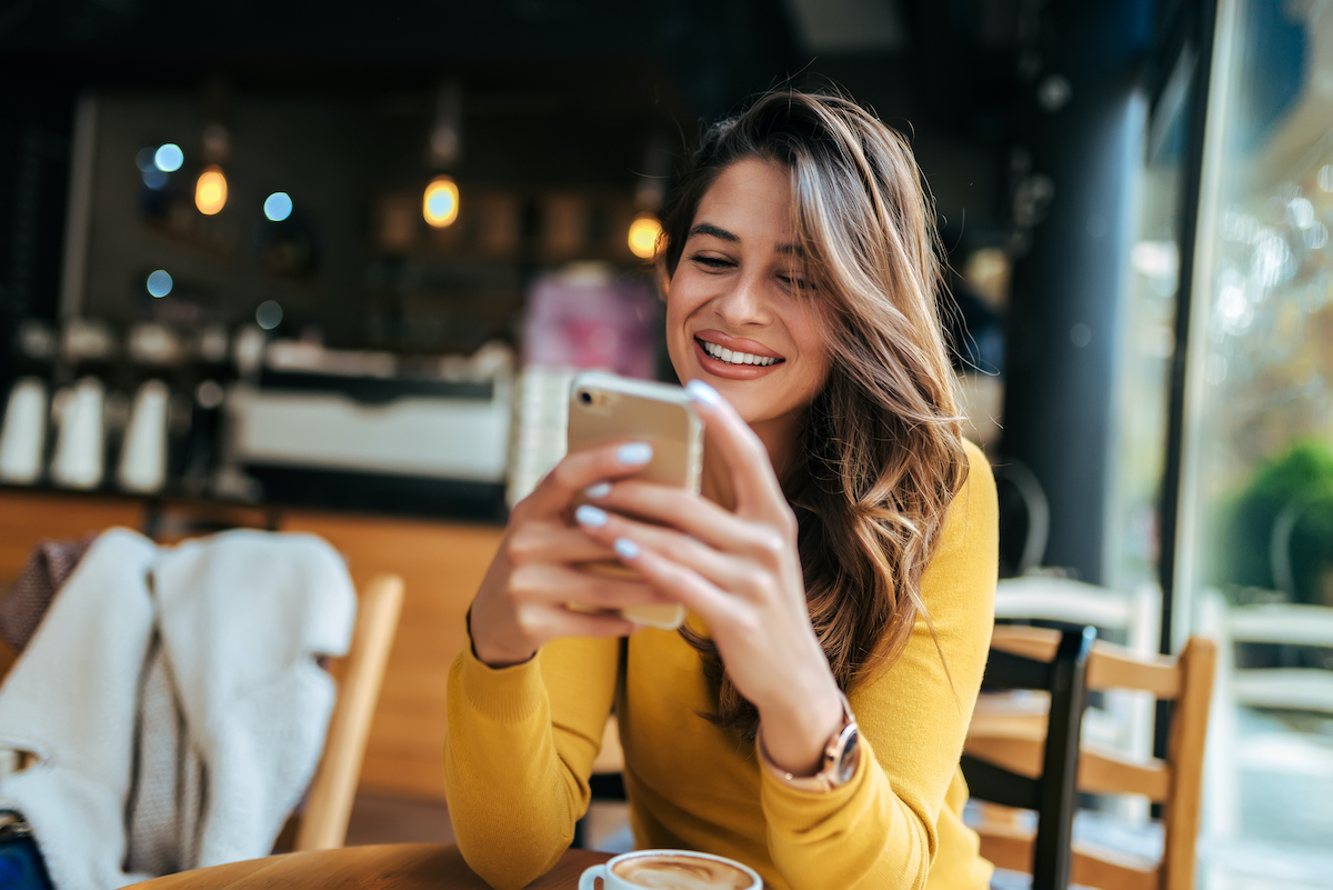 happy woman looking at smartphone