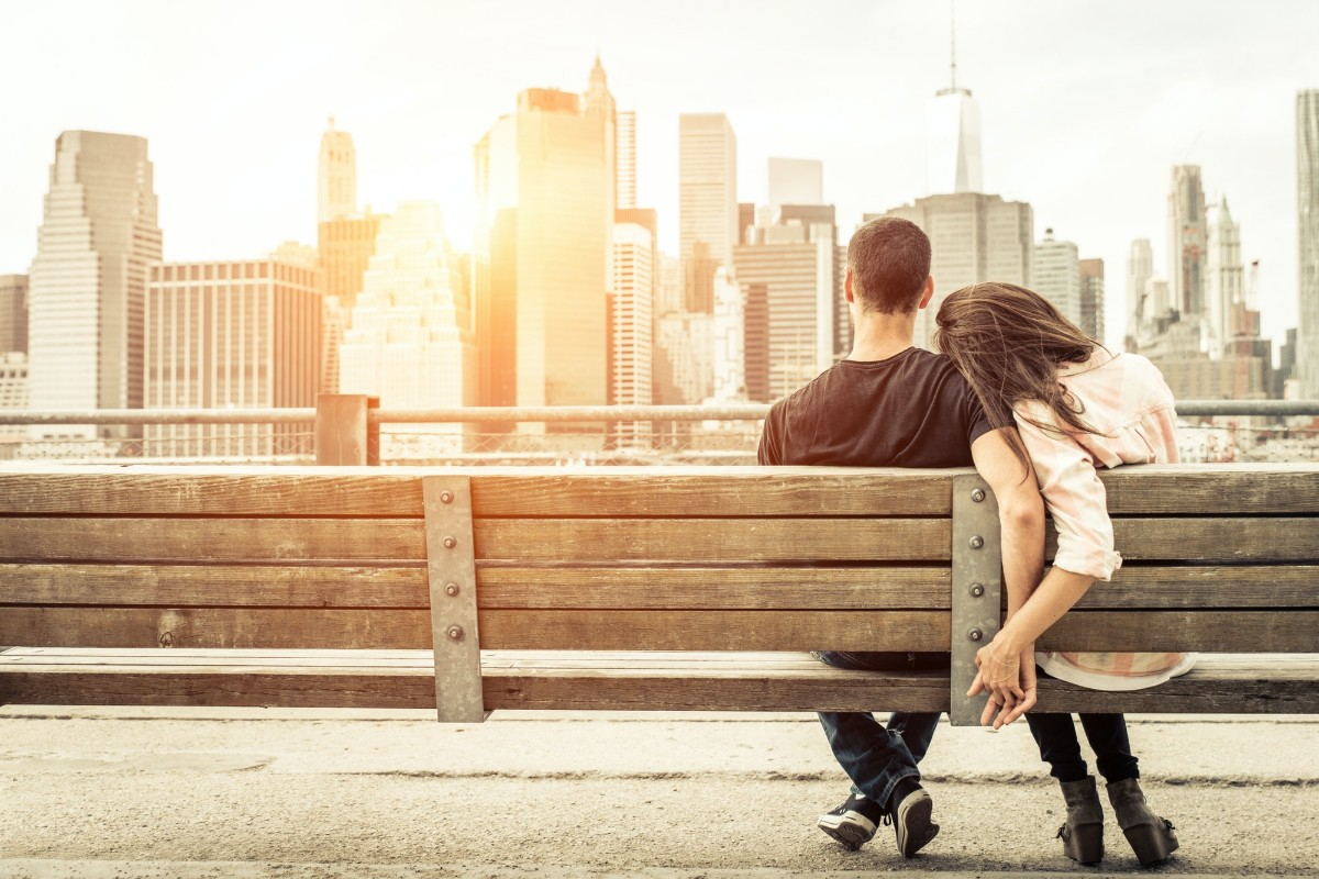 man and woman snuggling on a bench