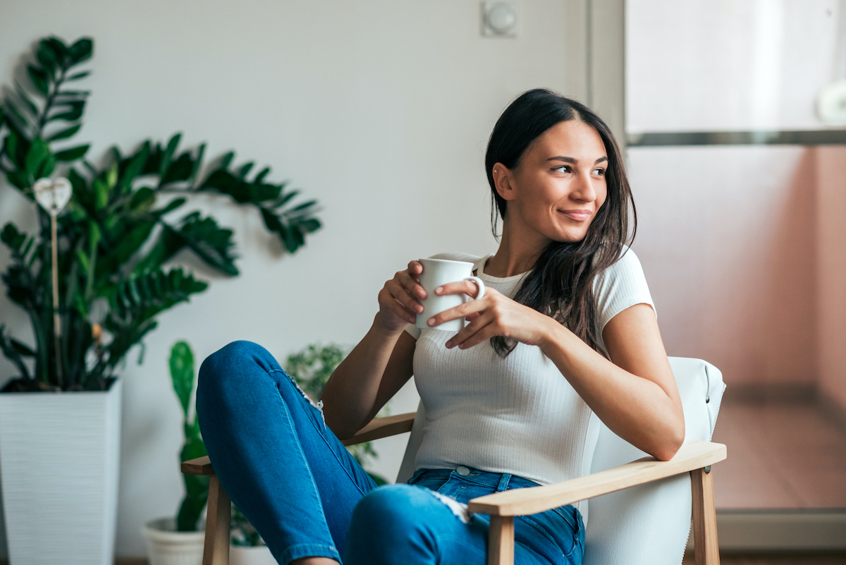 Beautiful young woman drinking coffee. Can adding this 1 spice to your coffee or tea help manage symptoms of PCOS?