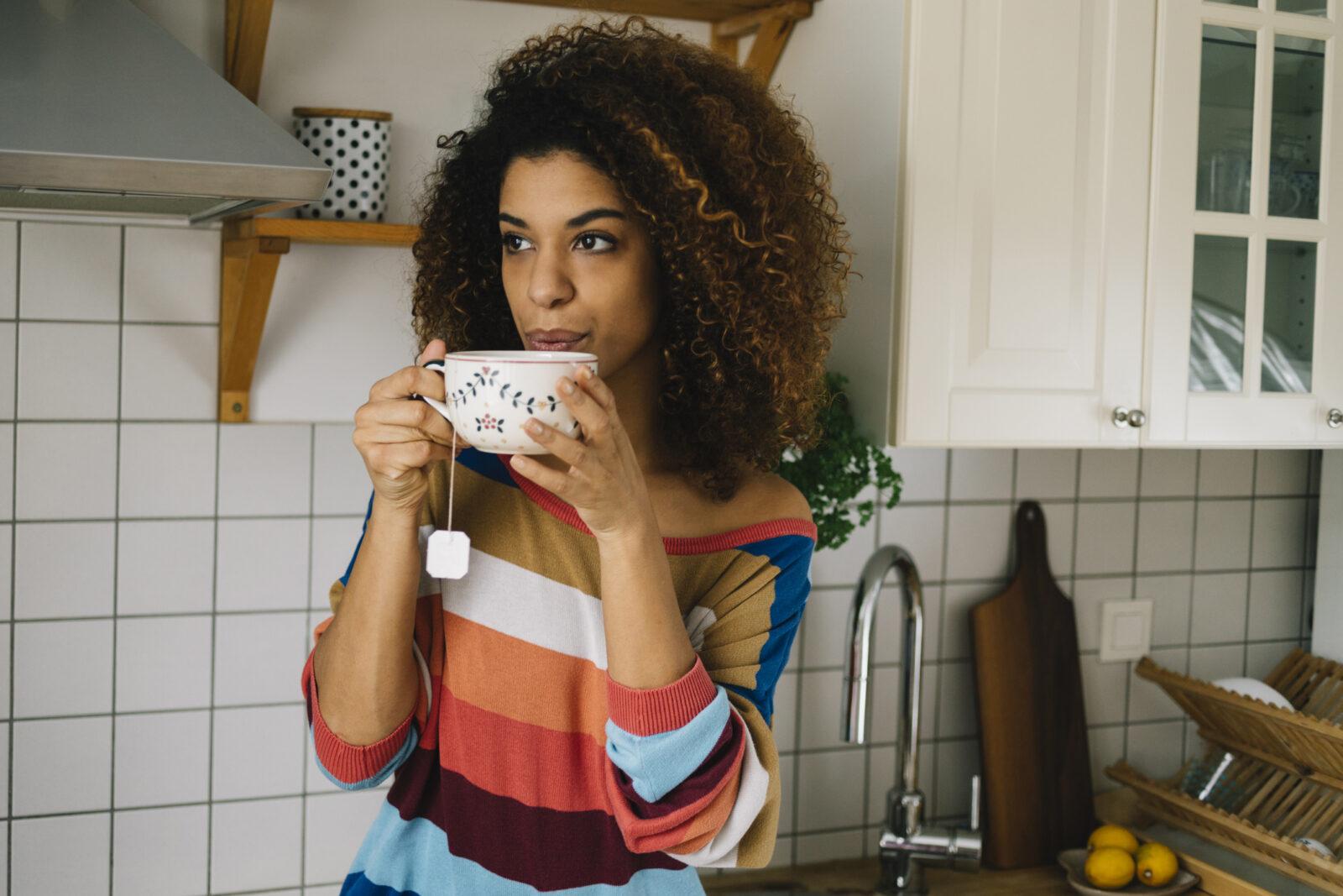 Beautiful young woman enjoying a cup of energizing caffeine free tea