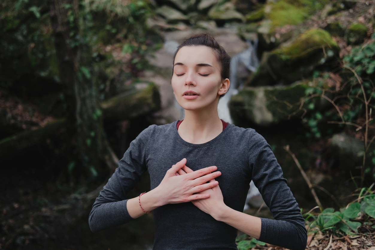 Young woman practicing breathing yoga pranayama outdoors in moss forest