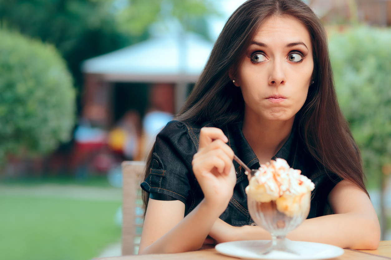 Young woman emotional eating ice cream