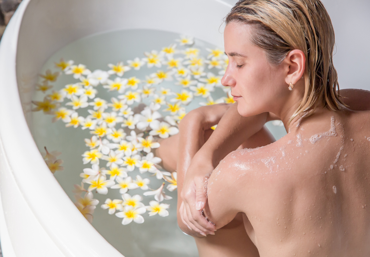 Beautiful young woman relaxing in bath with tropical flowers organic skin care